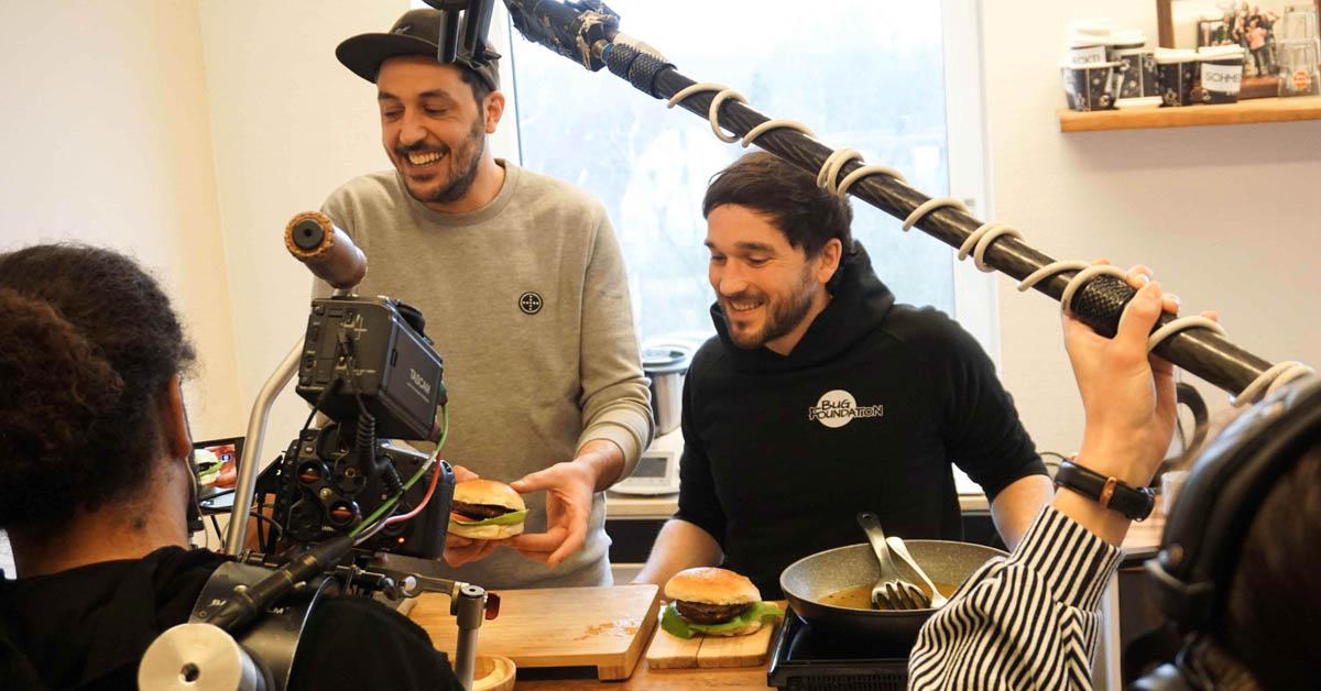 Die Gründer Baris Özel (links) und Max Krämer zeigen ihren Insektenburger im Fernsehinterview.